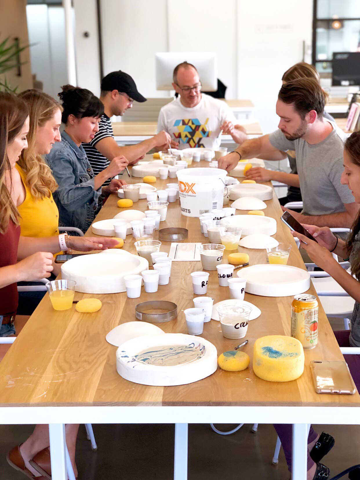 group of people sitting at a table filled with pottery supplies
