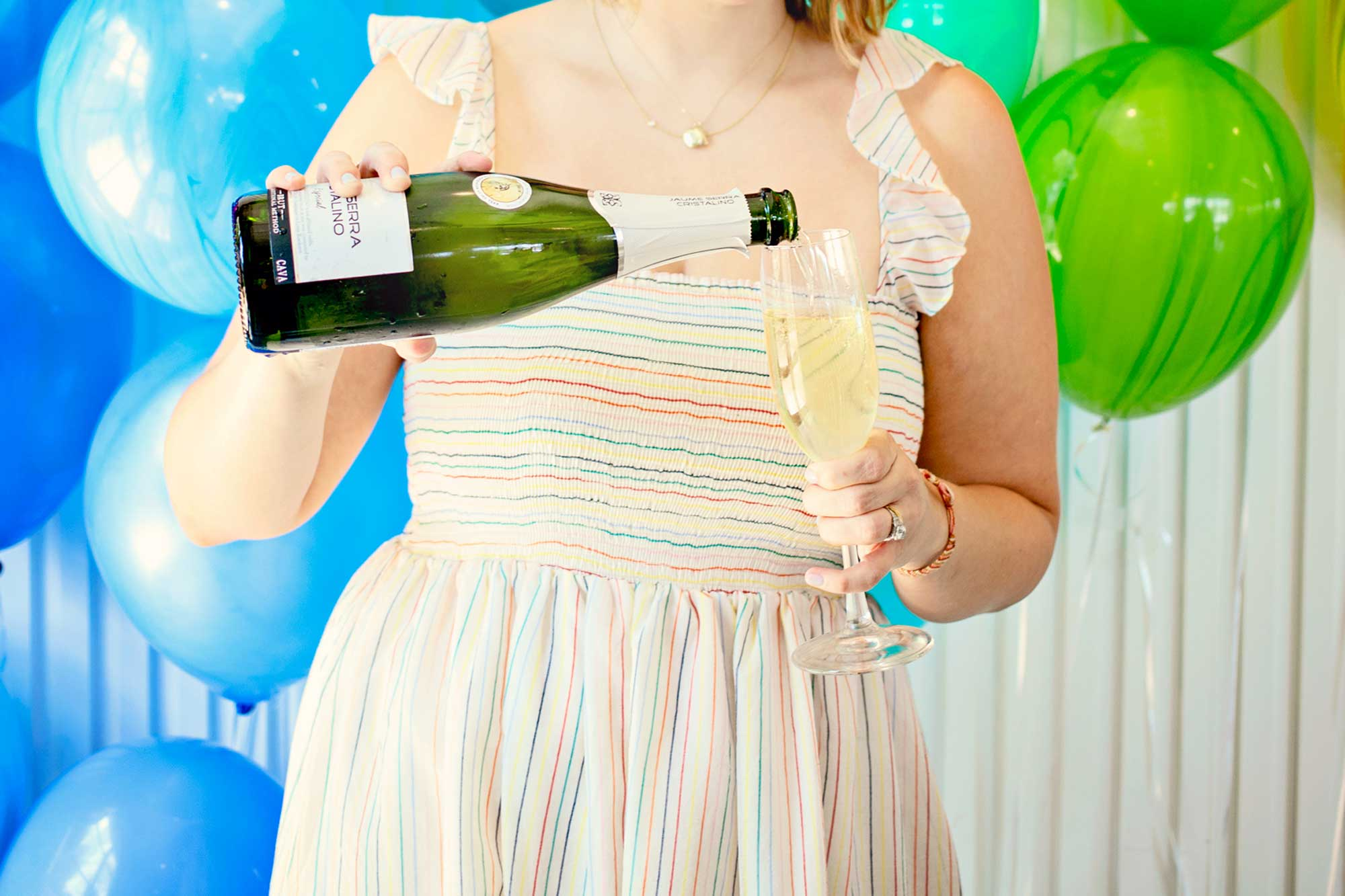 woman in rainbow dress pouring champagne into a flute in front of balloons