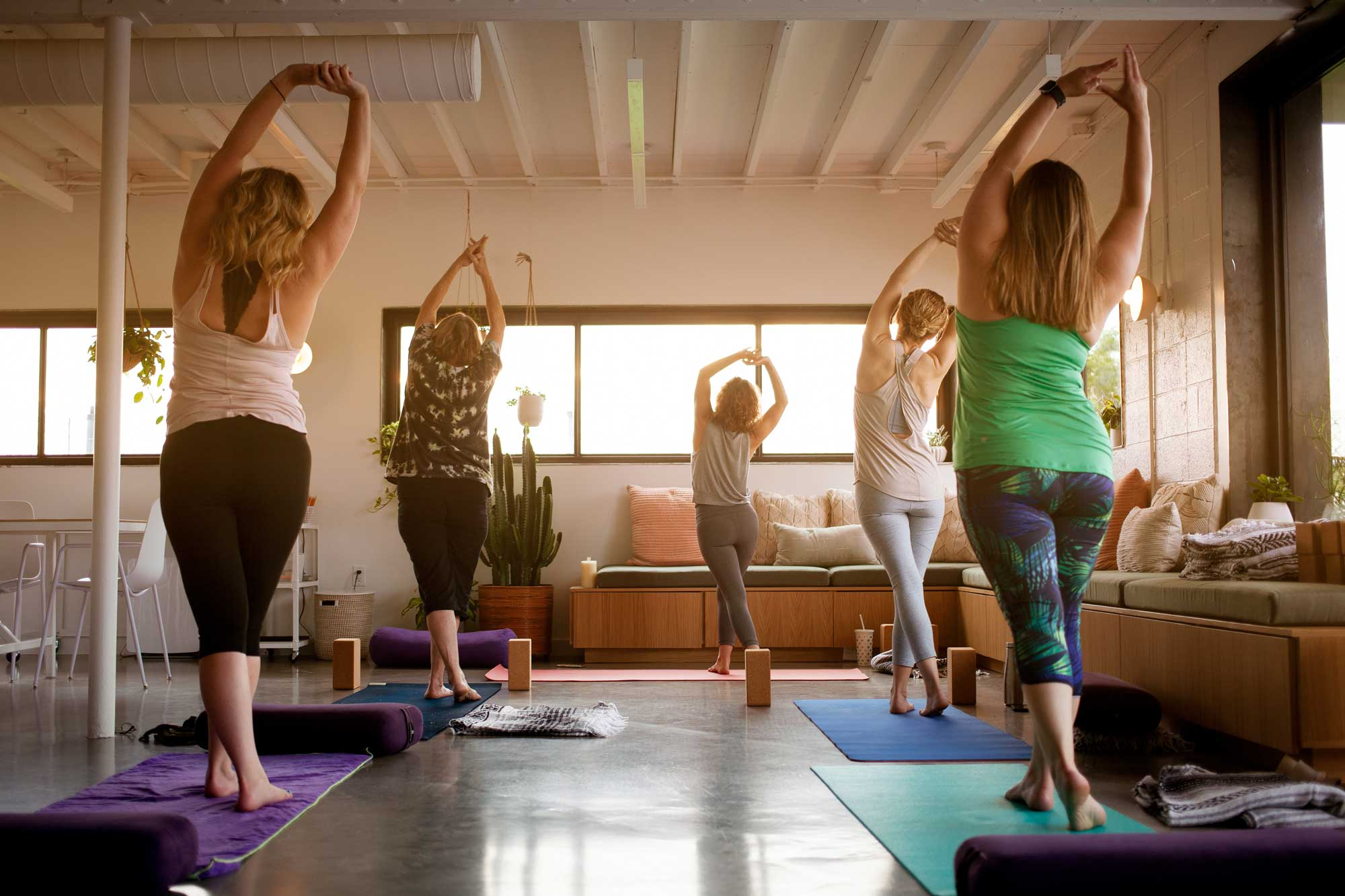 five women standing up doing yoga in an event space