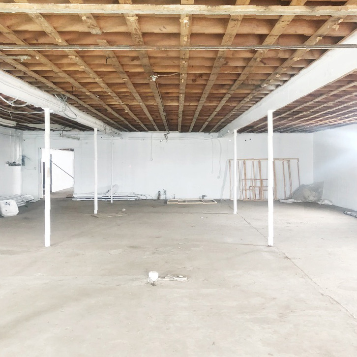 empty industrial building with wood rafter ceiling and bare concrete floor