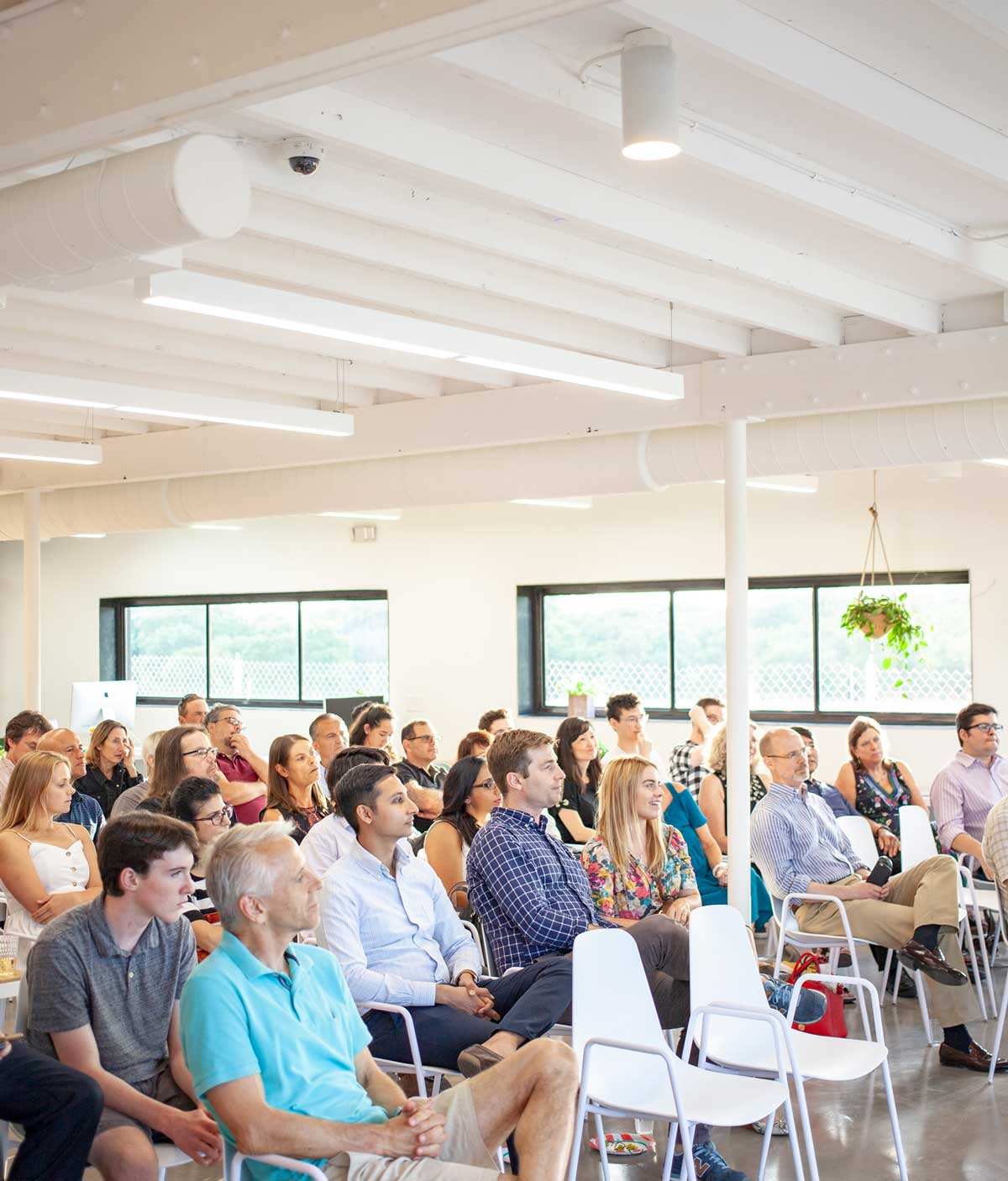 group of adults sitting in chairs during an event at a coworking space