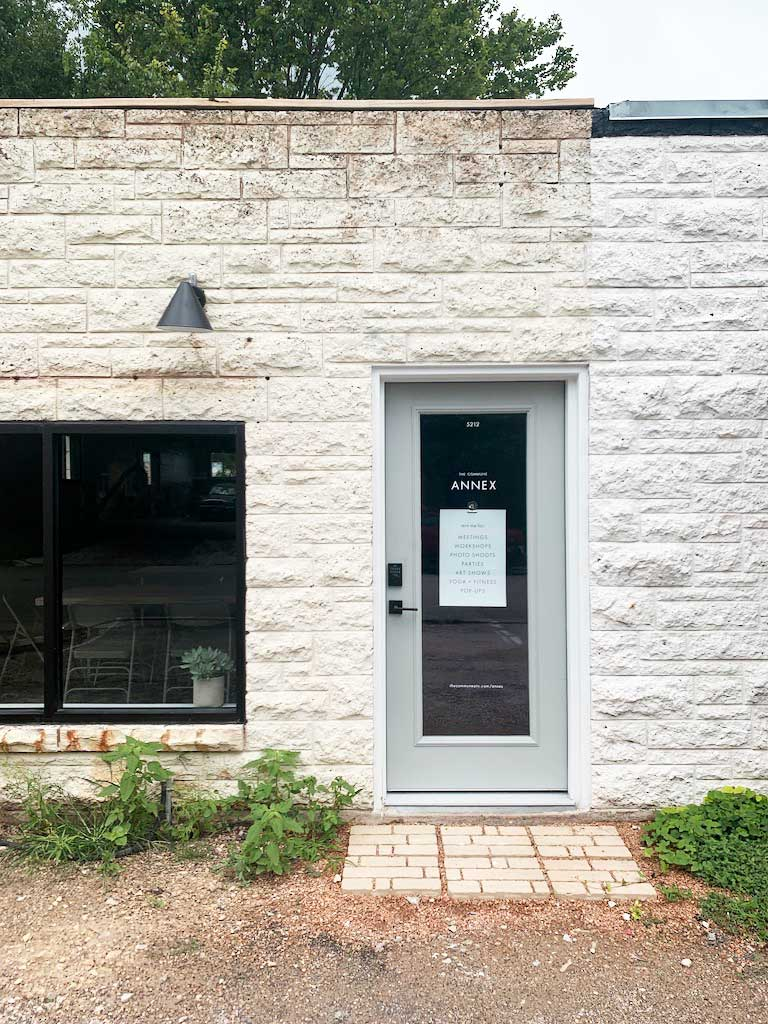 exterior of white stone small business with gray framed glass door and windows