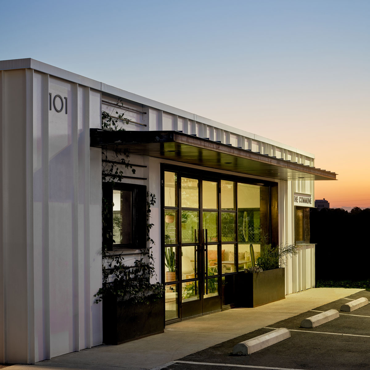 exterior of white metal coworking building with large windows as dusk